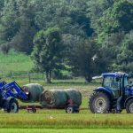 two tractors loading hay bales on a wagon