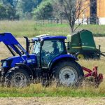 two tractors mowing and baling
